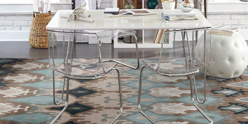 how to choose an area rug - a colorful, artistic rug under a modern acrylic table with clear acrylic chairs, and a white leather ottoman