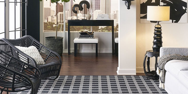 how to choose an area rug - a black, geometric pattern rug in a modern room with satrong black accents overlooking a city