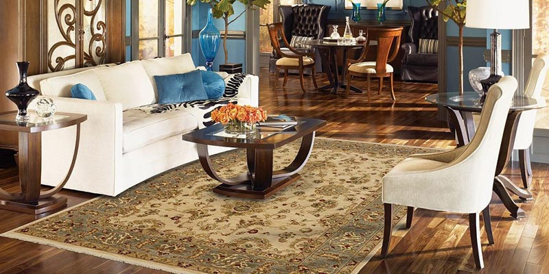 how to choose an area rug - a colorful room with a traditional rug under a wooden coffee table with blue acccent pillows, decor, and paint on the walls