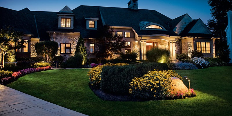 how to choose outdoor lighting - a house with outdoor path lights, outdoor recessed lighting, and landscape lighting