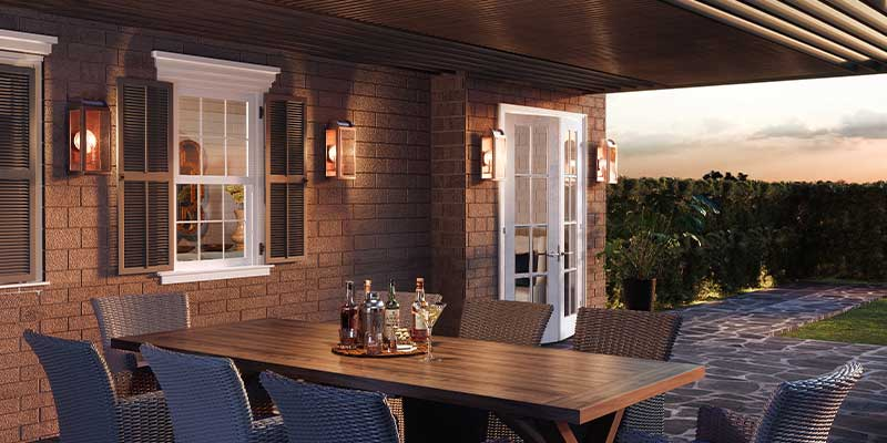 how to choose outdoor lighting - outdoor wall sconces under covered patio with wooden table and seating