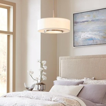 light pendant hanging over a bed with a natural color shceme