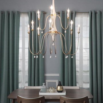 multi-light chandelier hanging in a living room with green curtains