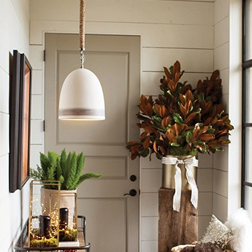 white rustic farmhouse pendant hanging in an entryway over a wood side table with ferns and twinkle lights