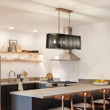 kitchen island light with a dark shade hanging in a modern kitchen