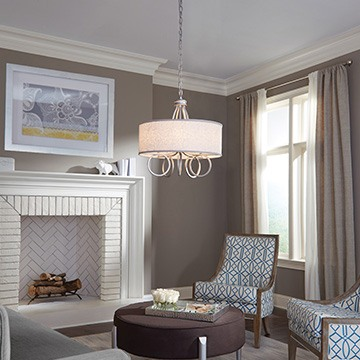 pendant with decorative rings hanging in a living room with grey walls and a large fire place